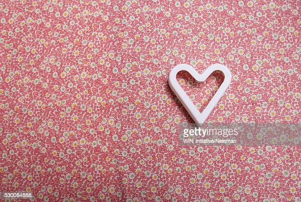 High angle view of a heart shape pastry cutter on a pink fabric