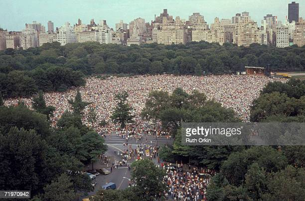 High angle view of a huge crowd gathered in the Central Park for an outdoor concert backed by a portion of the Manhattan skyline New York New York...