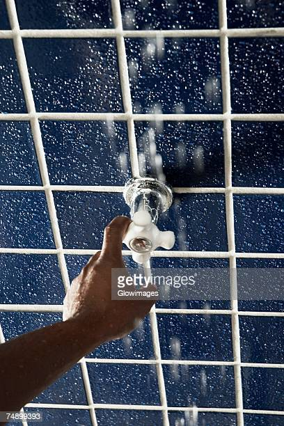 High angle view of a human hand turning a shower knob