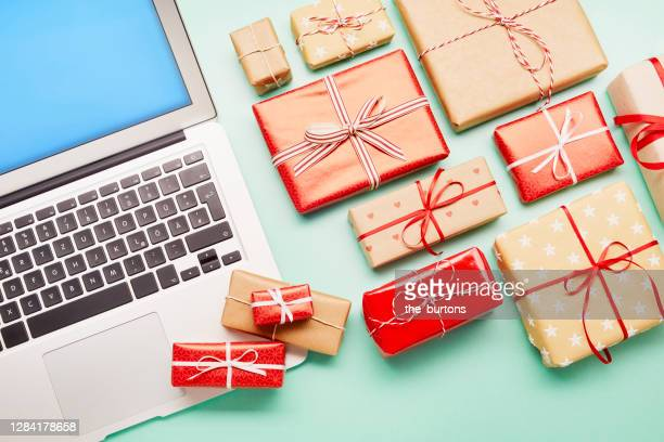 high angle view of a laptop computer and gifts on turquoise background, online shopping - holiday stock pictures, royalty-free photos & images