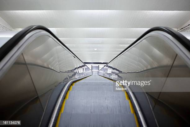 high angle view of a long escalator - hinunter bewegen stock-fotos und bilder