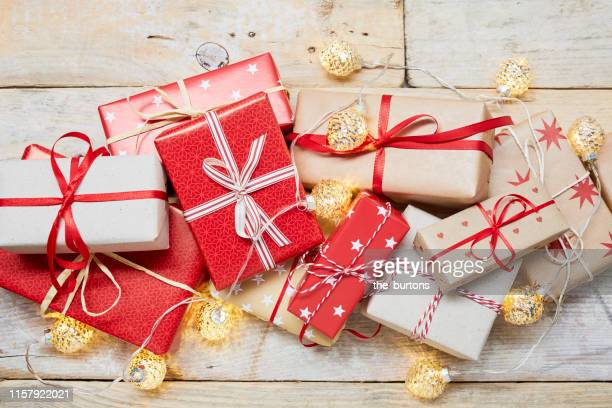high angle view of a lot of wrapped christmas gifts and strings lights on wooden background - geschenk stock-fotos und bilder