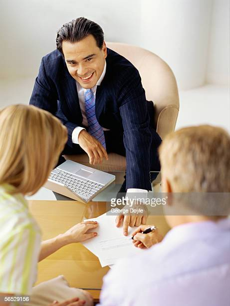 high angle view of a male real estate agent talking to a mid adult couple