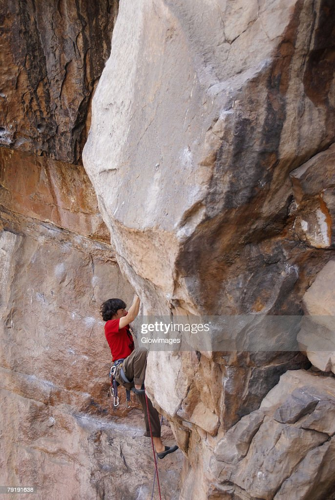 High angle view of a male rock climber scaling a rock face : Foto de stock