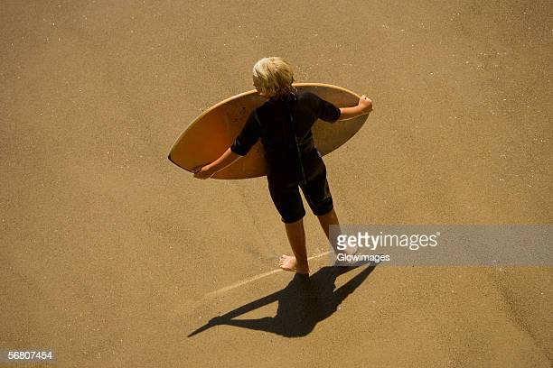 High angle view of a man carrying a boogie board on the beach