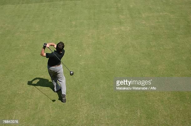 high angle view of a man playing a golf stroke - ゴルフクラブ ドライバー ストックフォトと画像