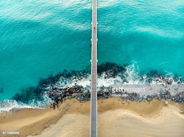 high angle view of a man running on wooden pier on beach - distant stock photos and pictures