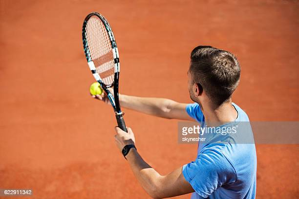 High angle view of a man serving tennis ball.