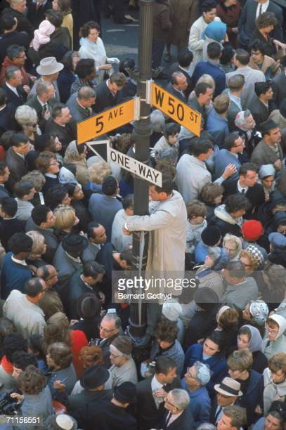 High angle view of a man who stands on a street post surrounded by swarming crowds who await the appearance of Polish religious leader Pope John Paul...