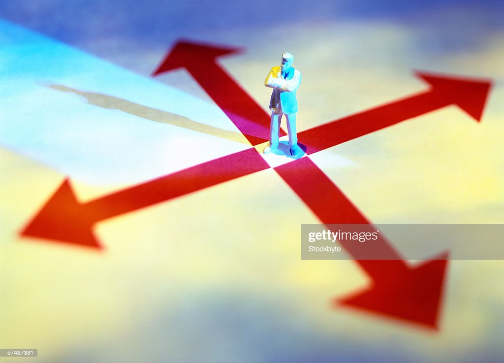 high angle view of a man's figure standing on a cross of arrows : Stock Photo