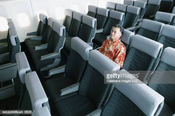 High angle view of a mature man traveling in an empty airplane