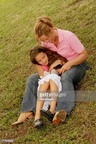 high angle view of a mature woman and her daughter reading a book in the park - little girls up skirt fotografías e imágenes de stock