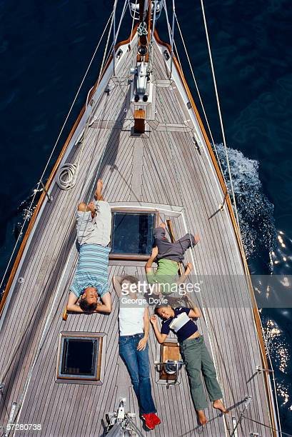 High angle view of a mid adult couple sunbathing with their two children on a sailboat