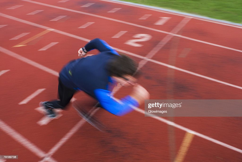 High angle view of a mid adult man at the starting line : Stock Photo