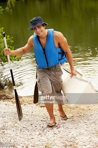 High angle view of a mid adult man carrying a kayak and an oar