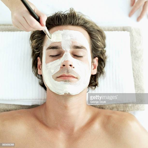 high angle view of a mid adult man getting a facial