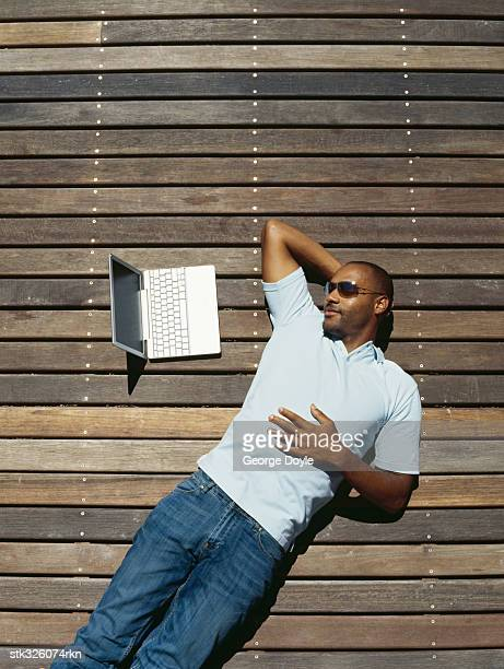 high angle view of a mid adult man lying down and looking at a laptop