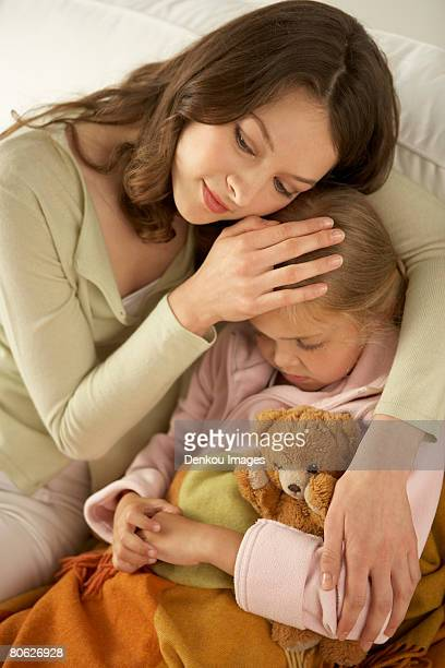 High angle view of a mid adult woman hugging her daughter