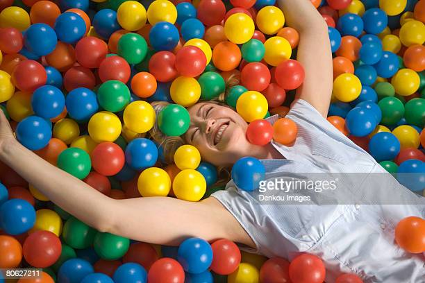 high angle view of a mid adult woman lying a in ball pool - spielball stock-fotos und bilder