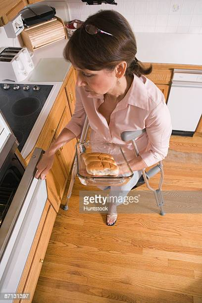 high angle view of a middle-aged disabled woman holding breads in a baking tray - amputee woman stock-fotos und bilder