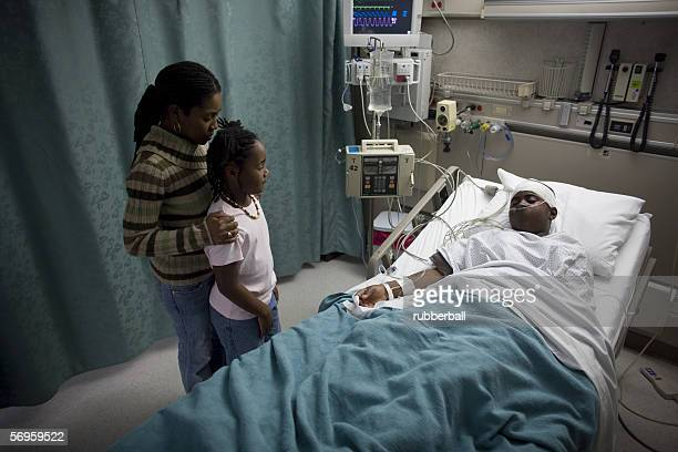 high angle view of a mother and daughter in a hospital looking at a teenage boy - patients brothers stock pictures, royalty-free photos & images