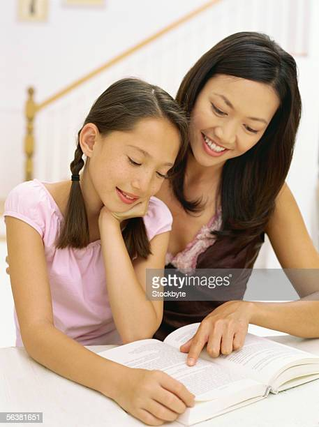 high angle view of a mother and her daughter reading a book