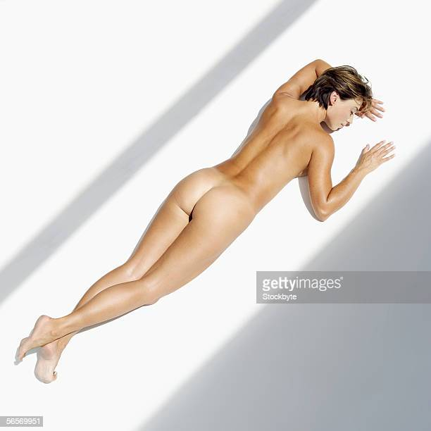high angle view of a naked young woman lying on the floor