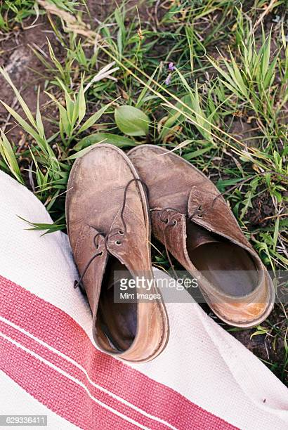 High angle view of a pair of worn brown leather lace up shoes on a picnic blanket.
