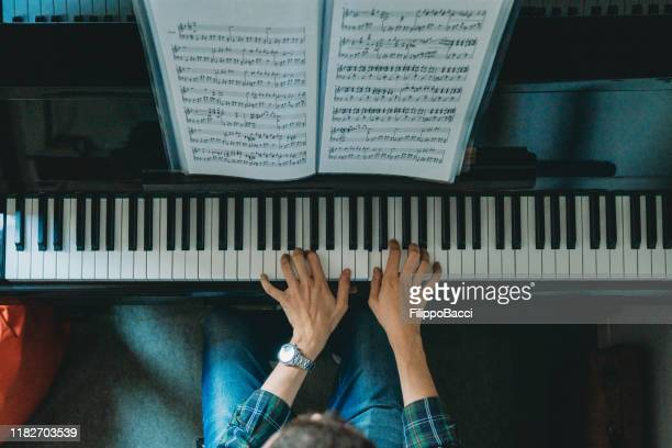 high angle view of a pianist playing piano - pianoforte foto e immagini stock