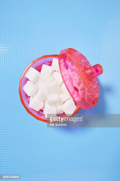high angle view of a pink bowl full of sugar cubes - sugar bowl stock photos and pictures