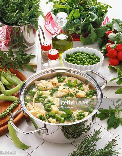 high angle view of a pot of soup with green peas served on a table with condiments and assorted herbs