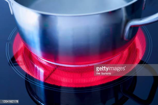 high angle view of a pot with boiling water on a heated ceramic stove top - burner stove top stock pictures, royalty-free photos & images