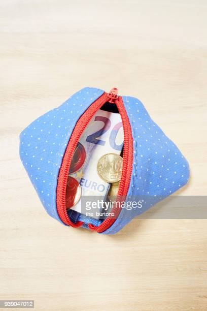 high angle view of a purse full of euro coins and twenty euro banknote - blue purse stock pictures, royalty-free photos & images