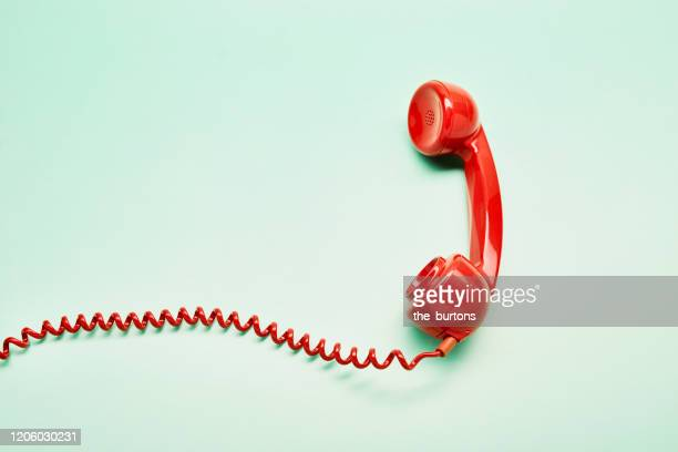 high angle view of a red old-fashioned telephone receiver with a coiled cable on turquoise background - antico condizione foto e immagini stock