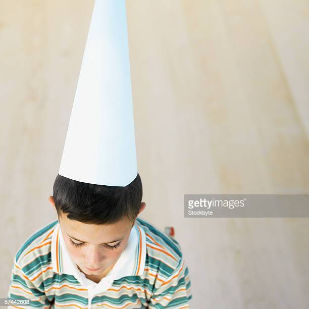 high angle view of a schoolboy (8-9) wearing a dunce cap - dunce cap stock pictures, royalty-free photos & images