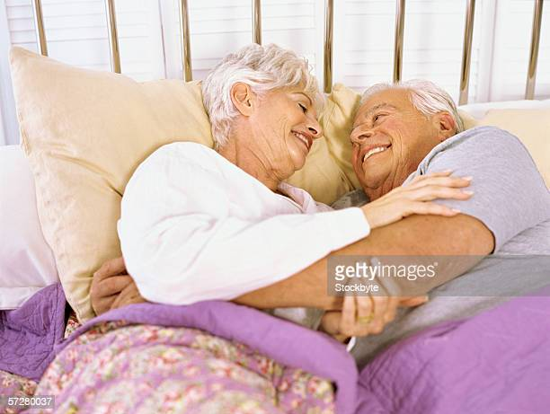 high angle view of a senior couple lying on the bed, hugging - 69 position stock photos and pictures