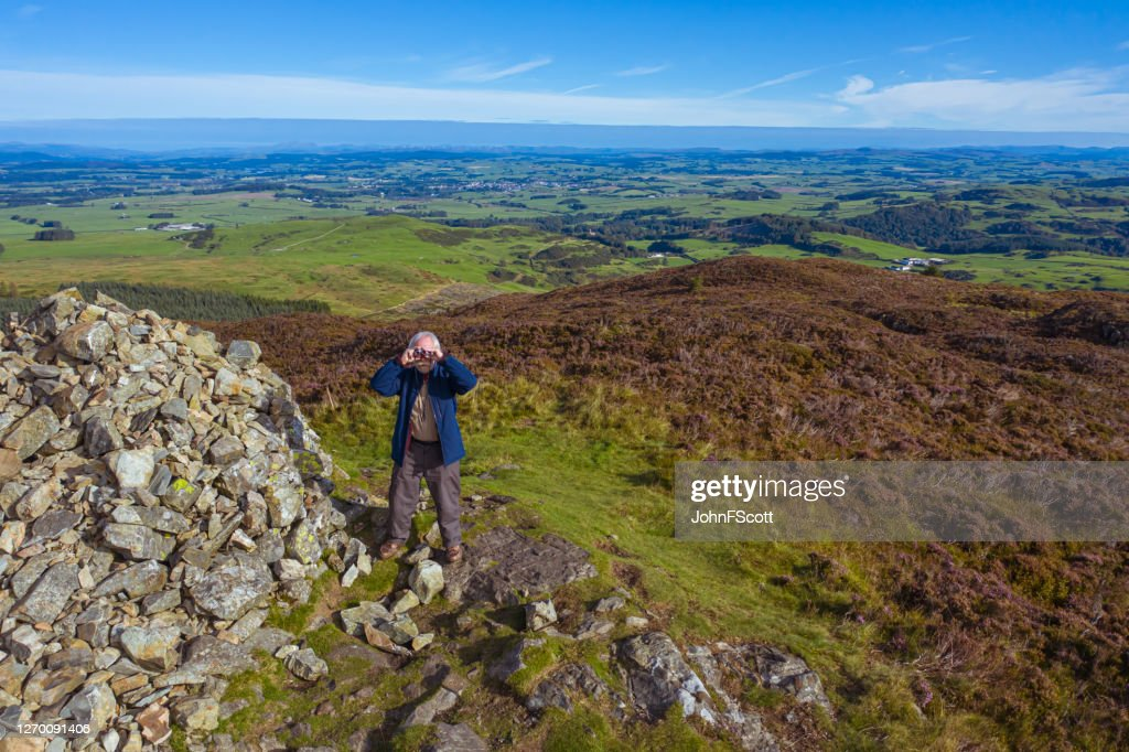 High angle view of a senior man using binoculars while standing next to a cairn on a Scottish hilltop : Stock Photo