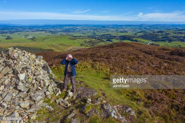 high angle view of a senior man using binoculars while standing next to a cairn on a scottish hilltop - johnfscott stock pictures, royalty-free photos & images