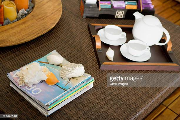 High angle view of a serving tray and magazines on a table