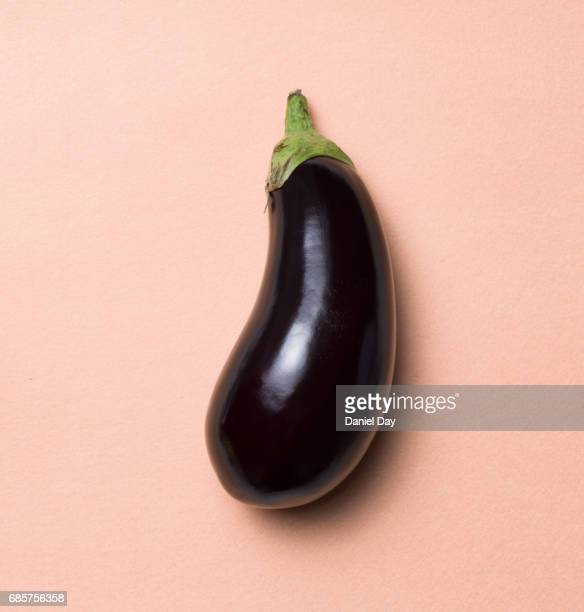 High angle view of a single aubergine on a pink flesh background