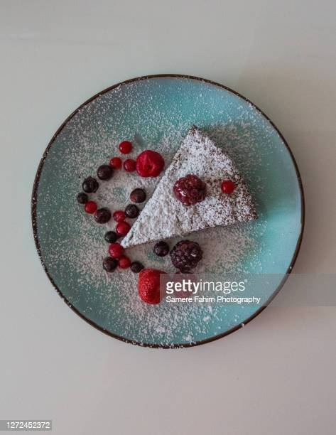 high angle view of a slice of chocolate cake accompanied by berries - hainaut stock pictures, royalty-free photos & images