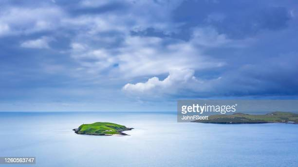 high angle view of a small island just off the coastline in a stretch of sea in south west scotland - johnfscott stock pictures, royalty-free photos & images