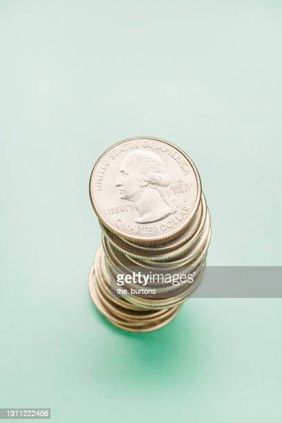 high angle view of a stack of us quarter coins on turquoise colored background - twenty five cent coin stock pictures, royalty-free photos & images