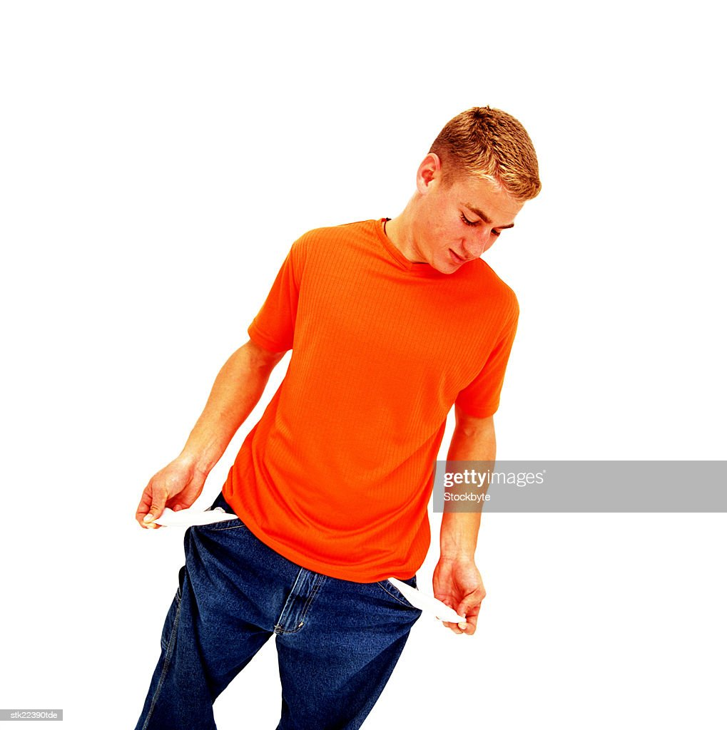 high angle view of a teenage boy looking at his empty pockets : Stock Photo