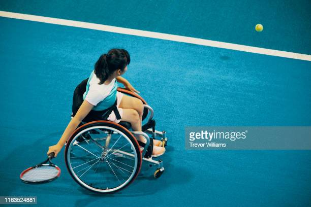 high angle view of a teenage girl playing and practicing wheelchair tennis at an indoor tennis court - 車いすテニス ストックフォトと画像
