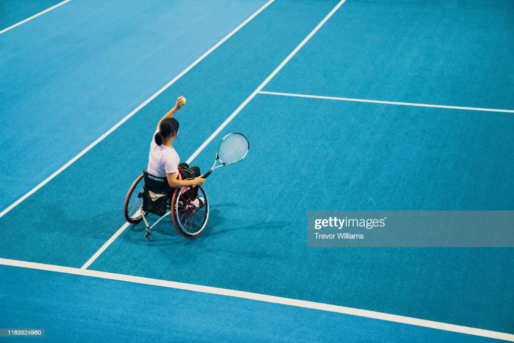 High angle view of a teenage girl playing and practicing wheelchair tennis at an indoor tennis court : Stock Photo