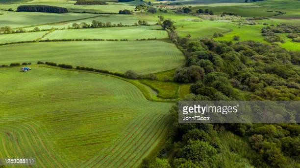 high angle view of a tractor leaving a field after cutting grass in rural dumfries and galloway, south west scotland. - johnfscott stock pictures, royalty-free photos & images