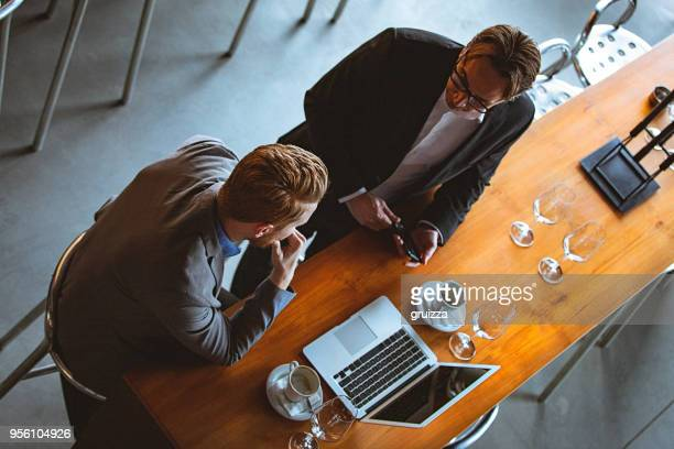 High Angle View of a Two Men Having a Conversation on a Coffee Break in a Cafe / Restaurant
