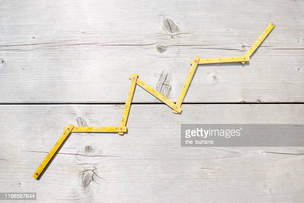 high angle view of a yellow folding ruler in shape of a stock curve on wooden background - measuring stock pictures, royalty-free photos & images