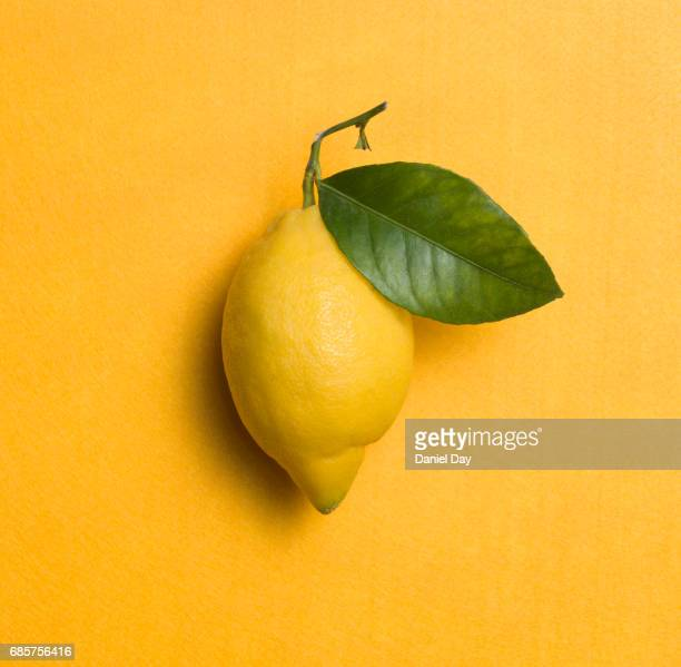 High angle view of a yellow lemon with a green leaf on a yellow background